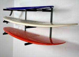 three surfboards on a wall rack
