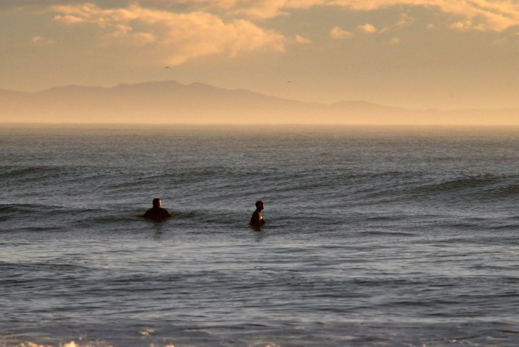 two surfers contemplating